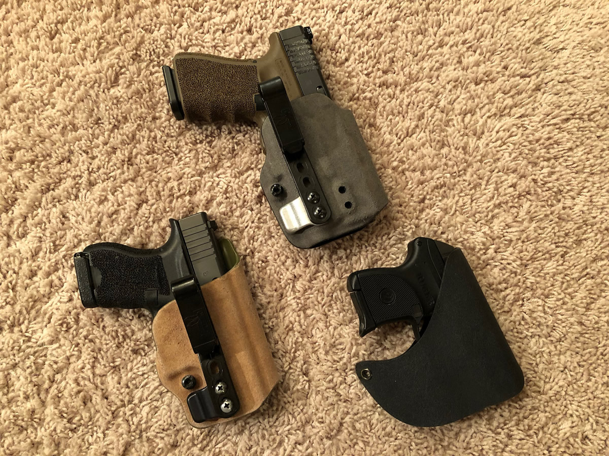 three holstered pistols